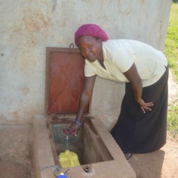 Teacher AgnesTeacher Agnes freut sich über Wasser in der Nabagereka Schule.